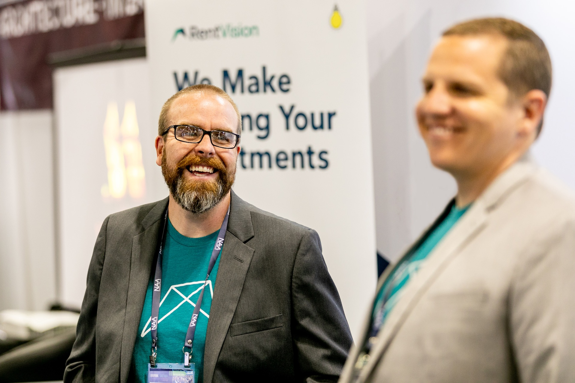 Two men wearing t-shirts with RentVision logo smiling in trade show booth.