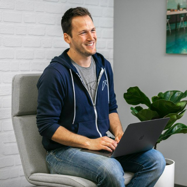 RentVision employee sitting on a chair with a laptop