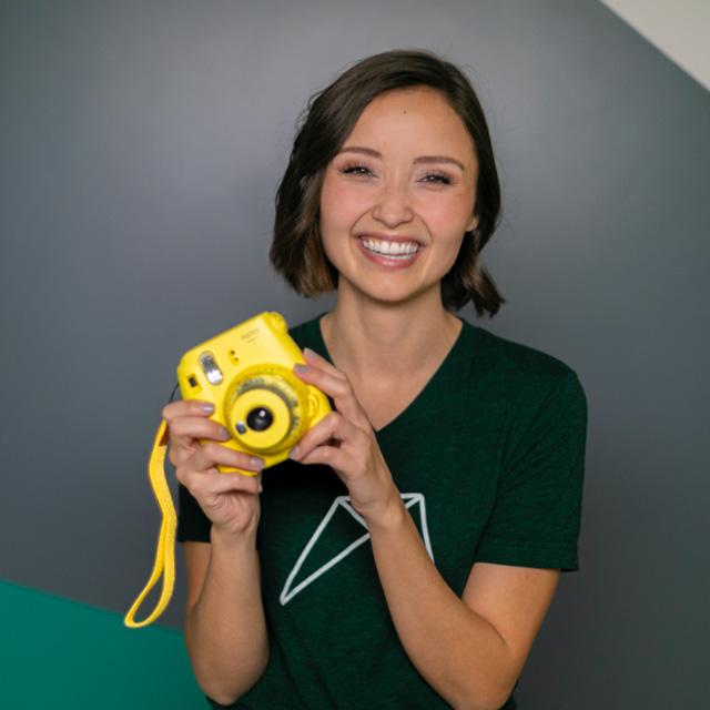 RentVision employee holding yellow polaroid camera