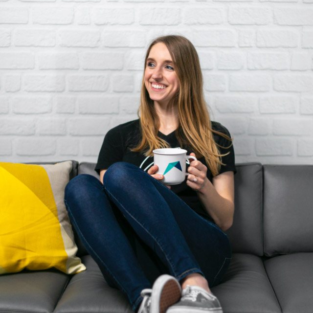 RentVision employee sitting on a couch with a coffee mug
