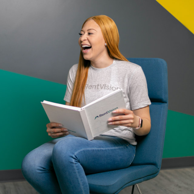 RentVision employee sitting on a chair with an open book